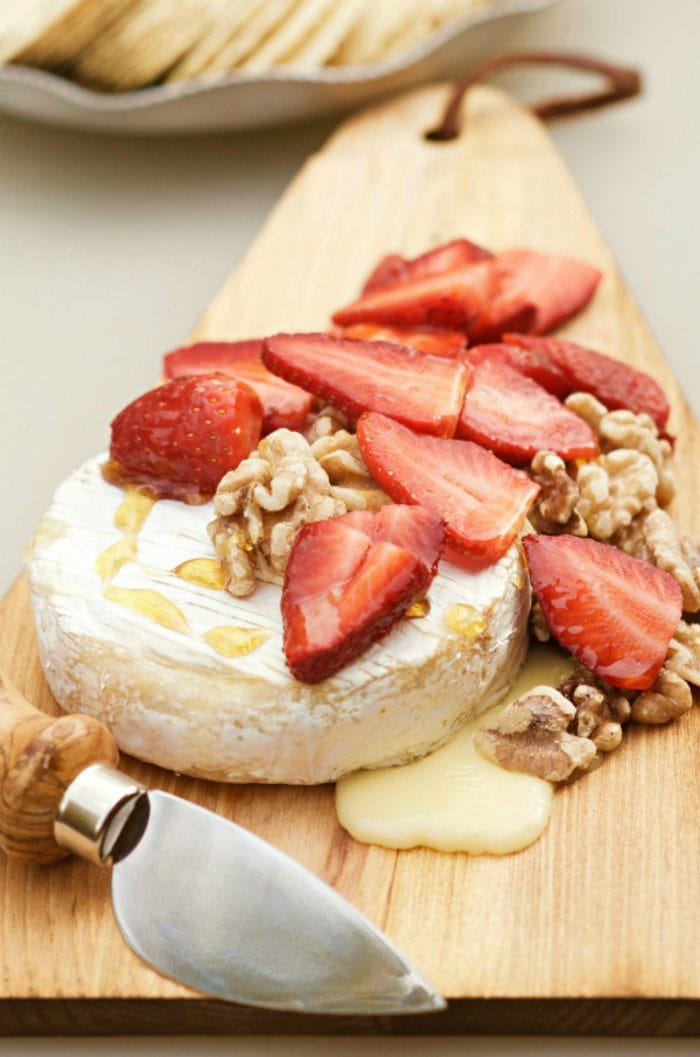 hot brie with fresh strawberries and toasted walnuts on top drizzled with honey