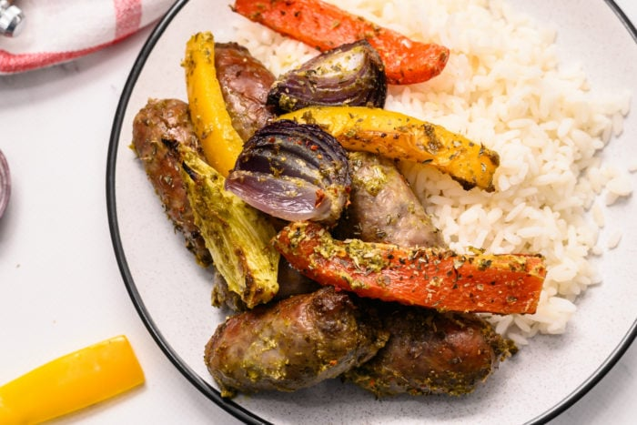 white plate with white rice, pesto brats, and peppers