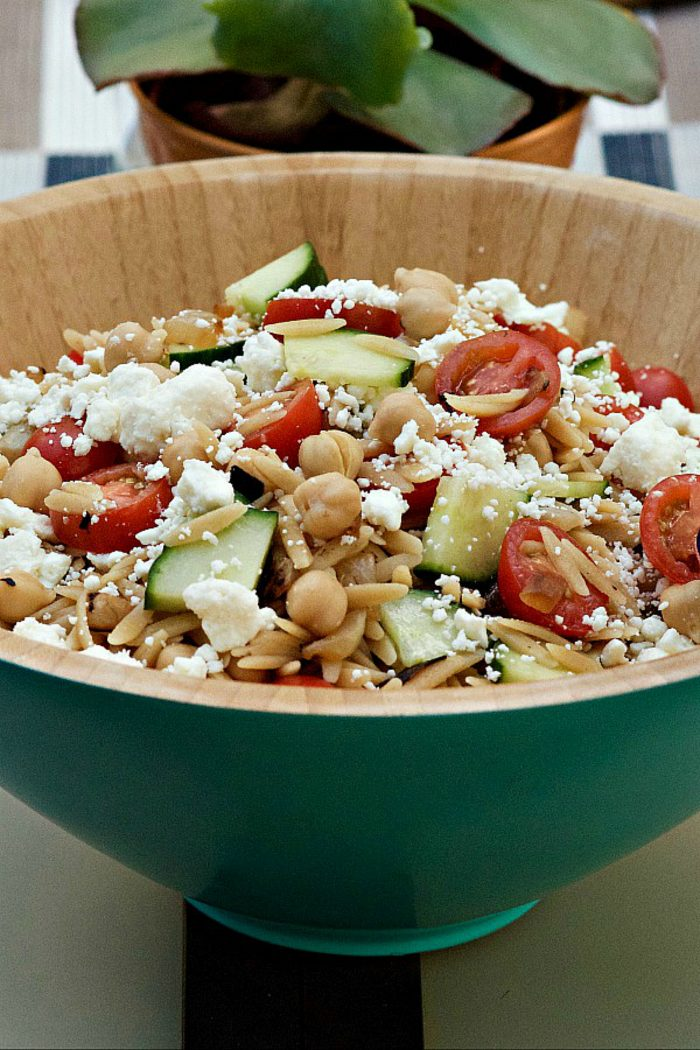 blue bowl filled with orzo salad with fresh tomatoes and feta