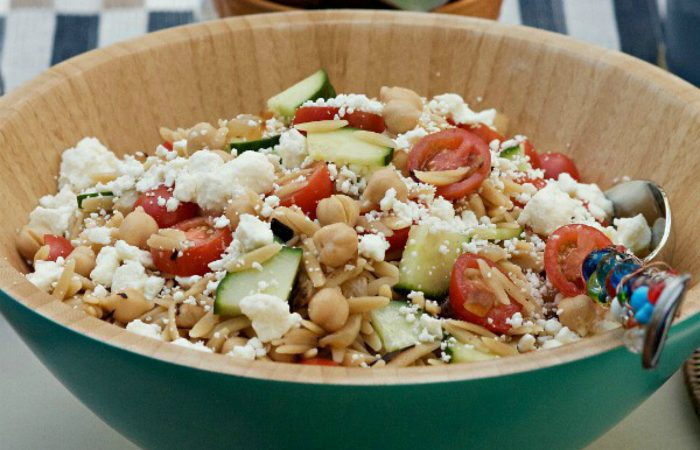 blue bamboo bowl filled with orzo salad with fresh tomatoes and feta cheese