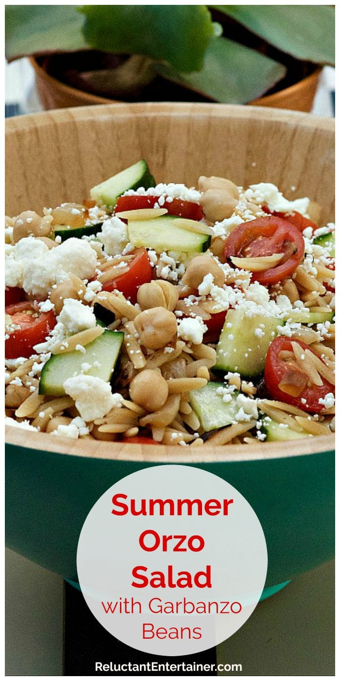 blue bamboo bowl filled with orzo salad with fresh tomatoes and feta cheese sprinkled on top