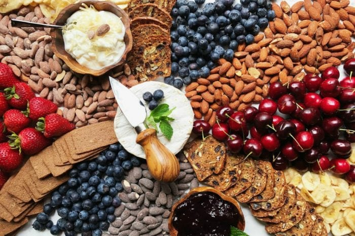 brie cheese on a board surrounded by crackers, almonds, and fresh fruit