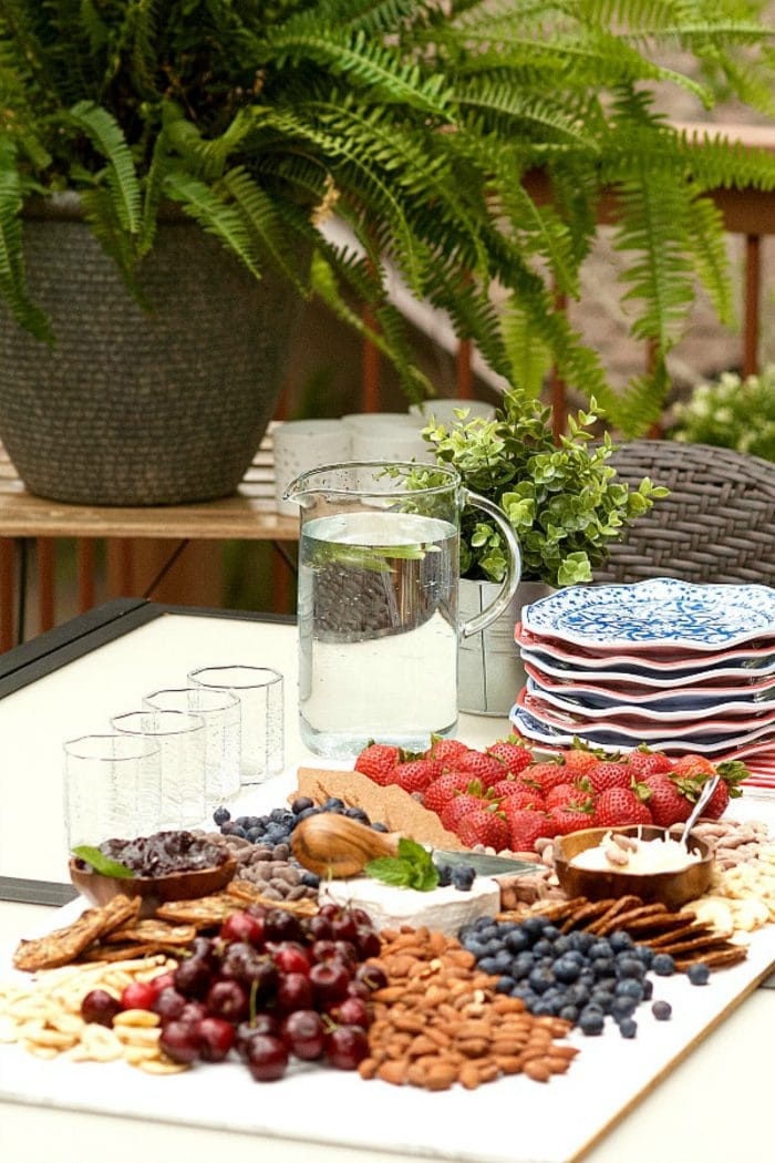 an outdoor setting with glasses, water pitcher, plates, and red, white and blue cheese board