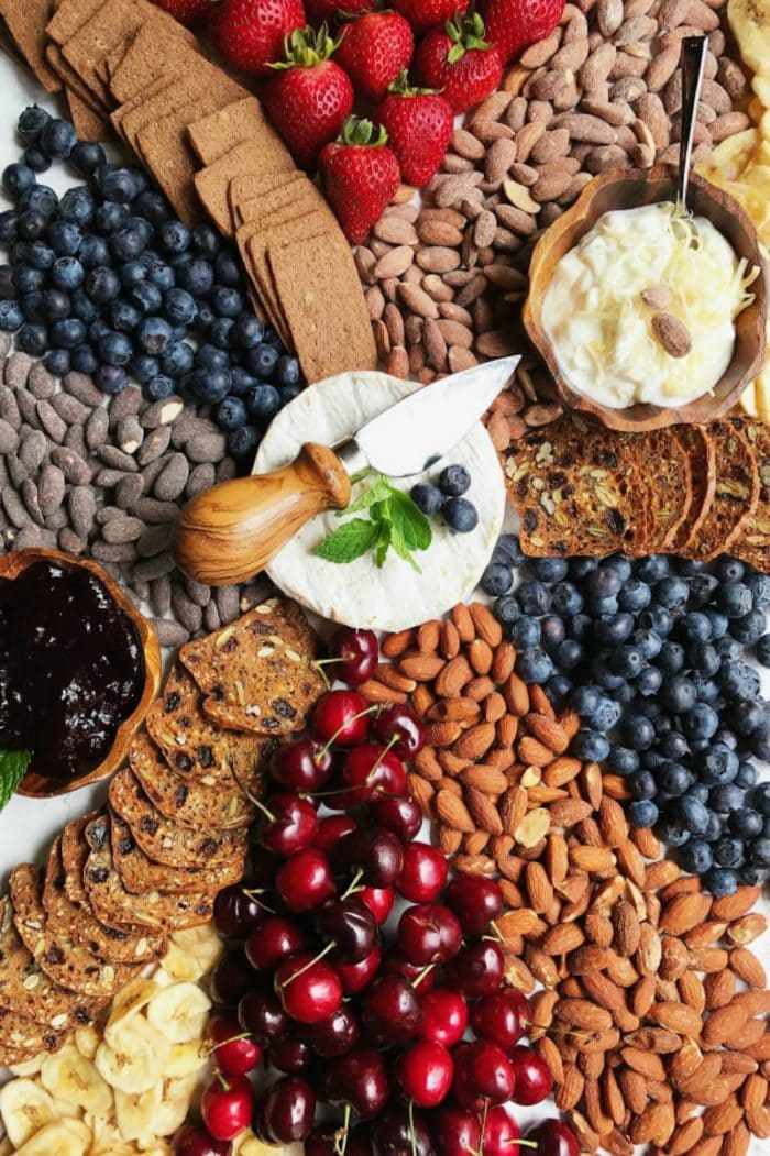 a cheese board with brie and almonds and berries