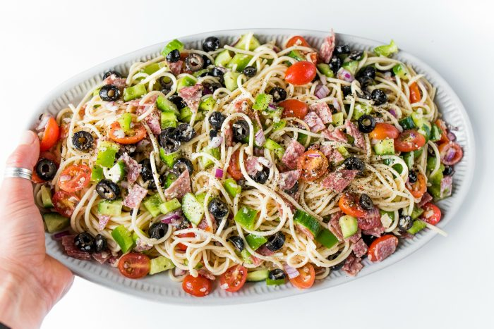 holding a plate of spaghetti salad