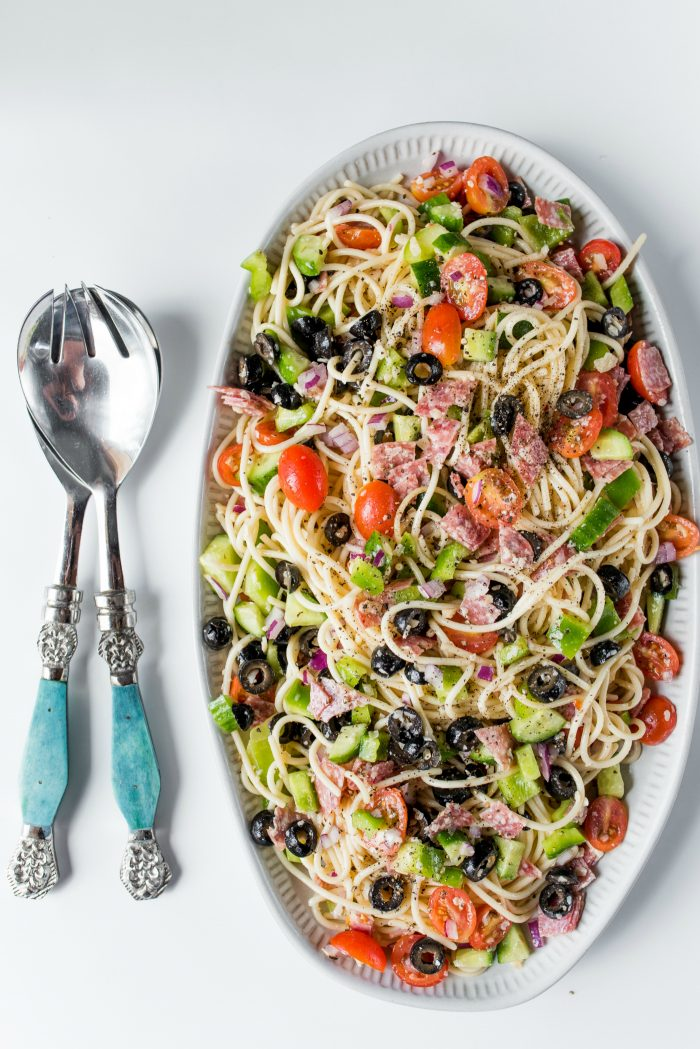 beautiful platter of italian spaghetti salad with blue salad tongs