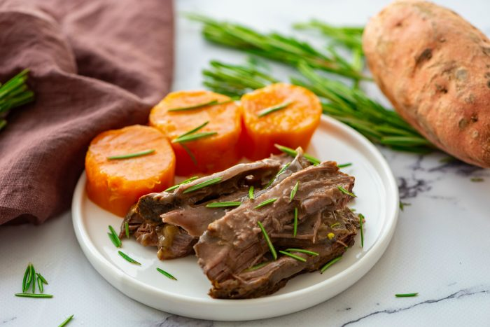 white plate with cooked roast beef with sweet potatoes, garnished with rosemary
