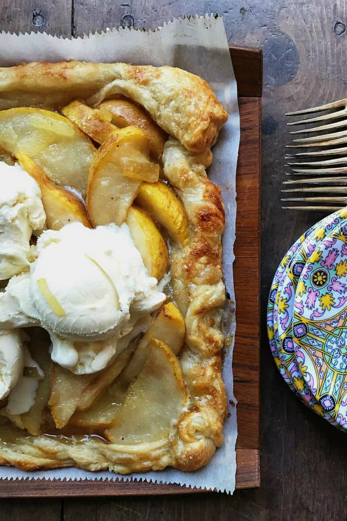 square puff pastry with pear on parchment paper