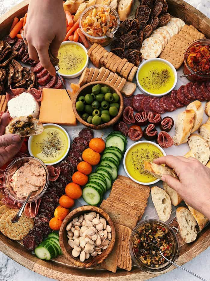 Hands dipping bread into olive oil and cutting cheese, on a giant Charcuterie Board