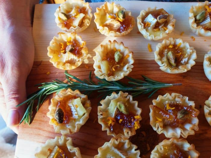 wood tray of Pistachio Brie Mini Tartlets