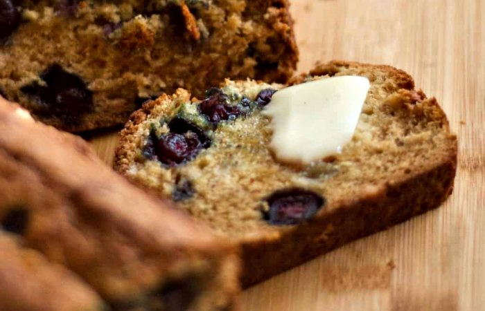 slice banana bread with blueberries and slab of butter