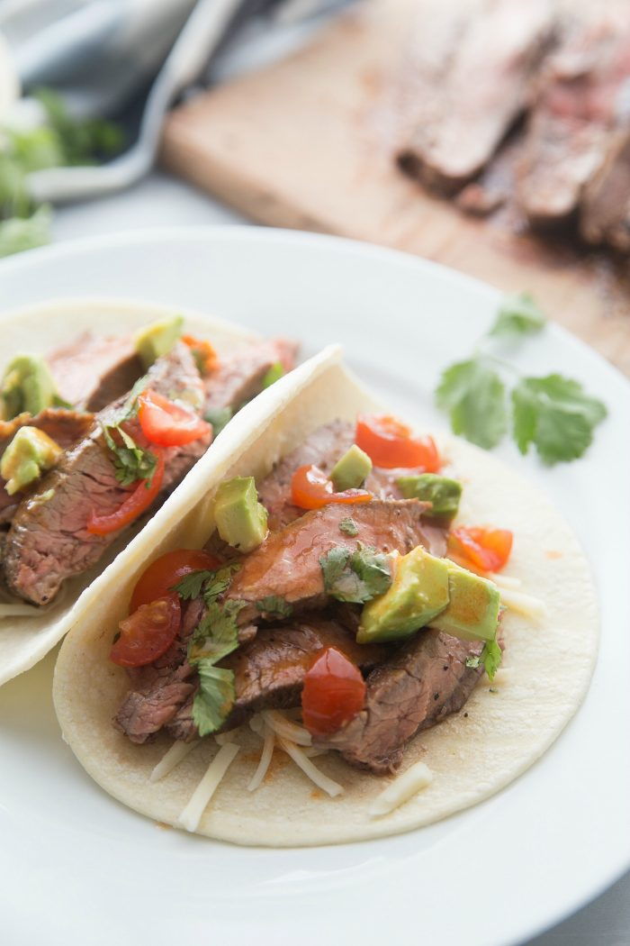 flank steak tacos with avocado, tomatoes, and cilantro