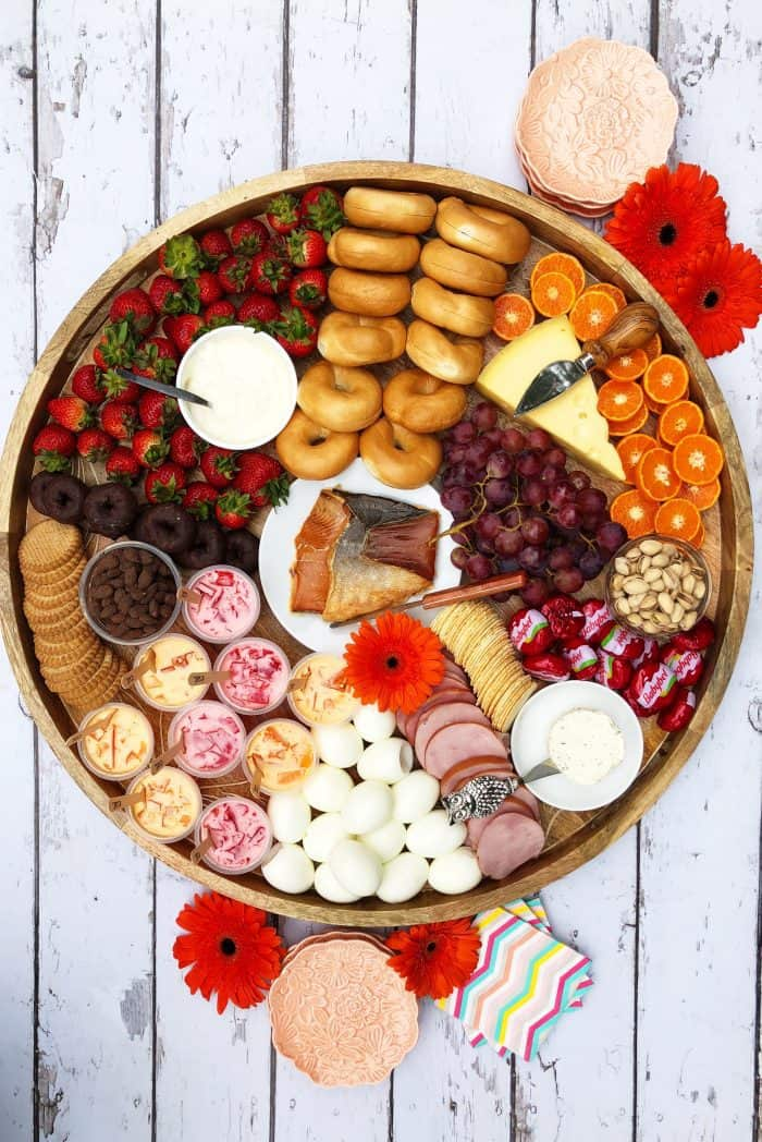 Big round beautiful Sunday Brunch Cheese Board with smoked salmon, boiled eggs, mini bagels, and more