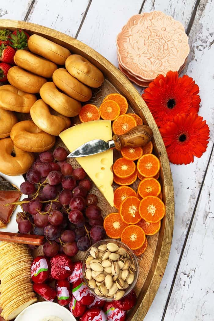 Big round beautiful Sunday Brunch Cheese Board with salmon, boiled eggs, mini bagels