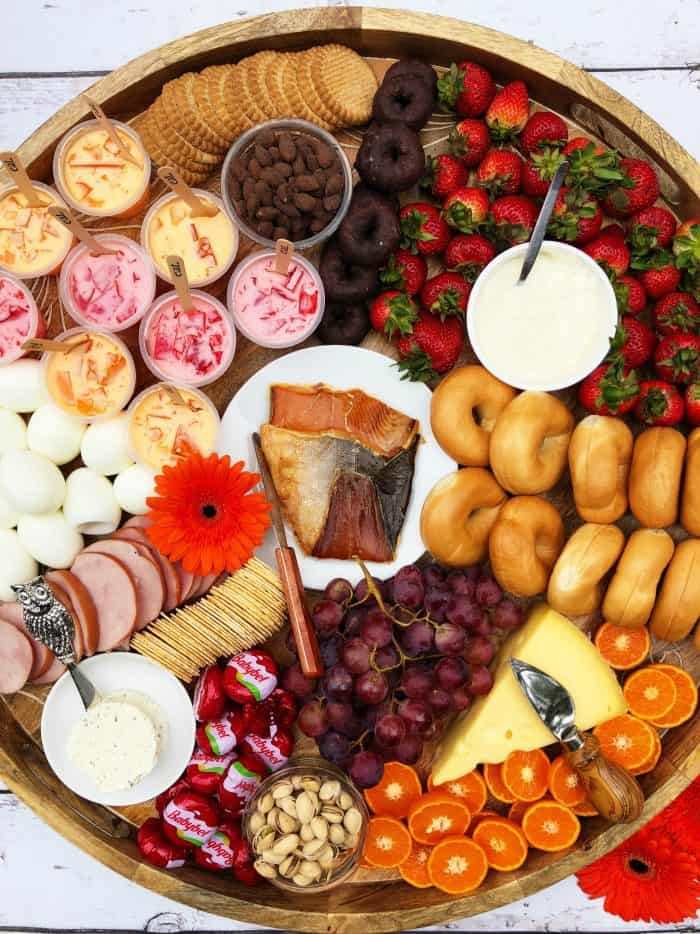 Big round Sunday Brunch Cheese Board with smoked salmon, boiled eggs, mini bagels, and more