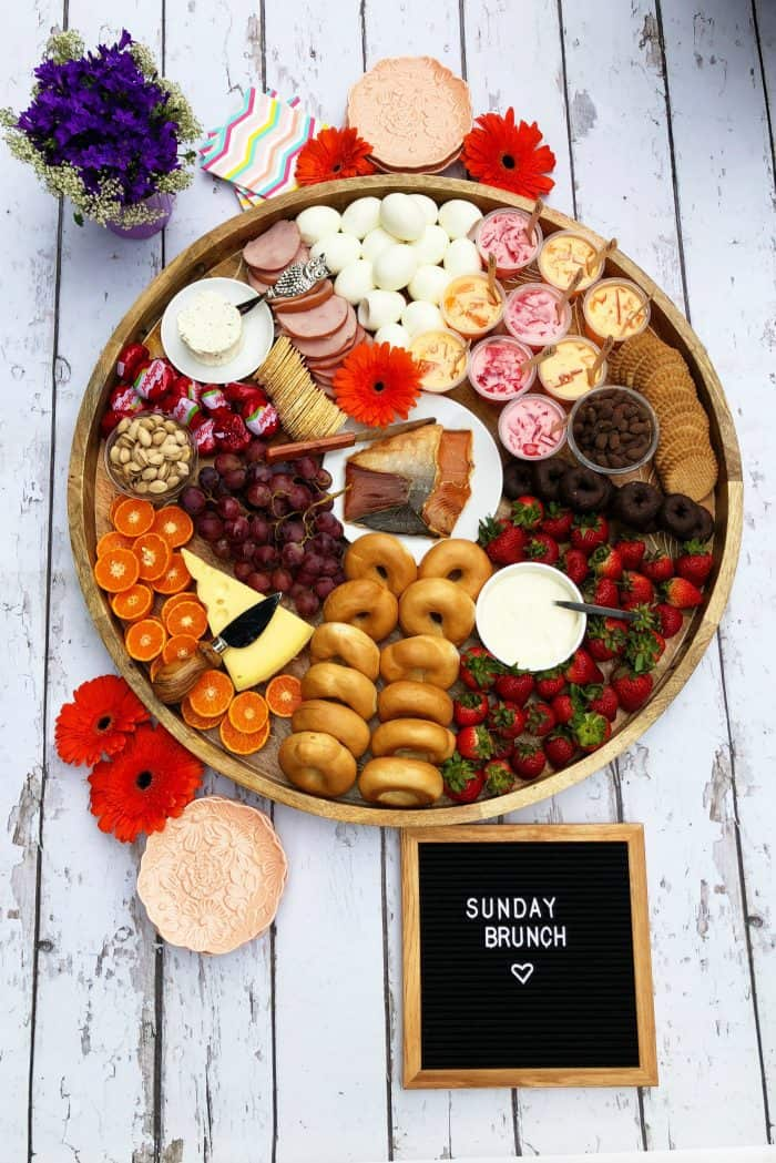 Big round beautiful Brunch Cheese Board with smoked salmon, boiled eggs, mini bagels, and more