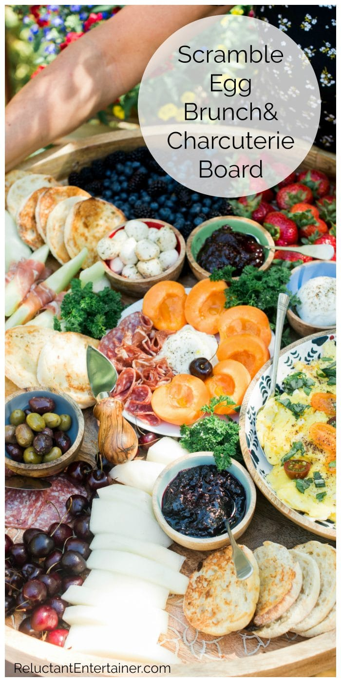 a breakfast spread with charcuterie meats, cheese, fruit, olive, and bowl of scrambled eggs