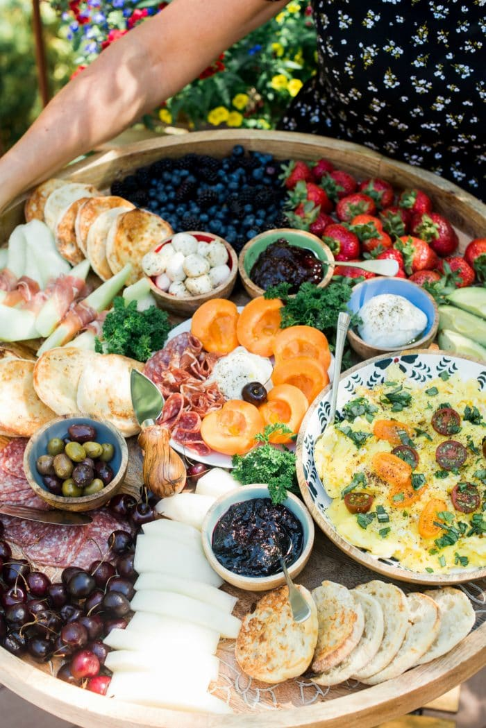 a round board filled with beautiful fruit, English muffins, a bowl of scrambleld eggs, meat, and cheese