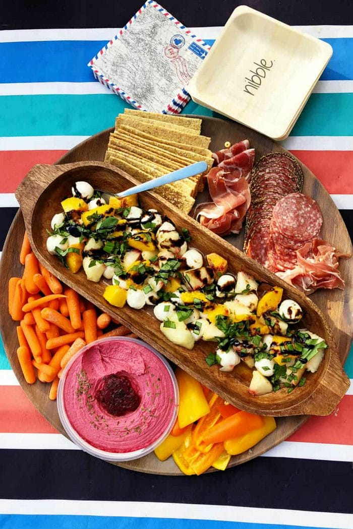 a round charcuterie board with peach caprese salad in the center