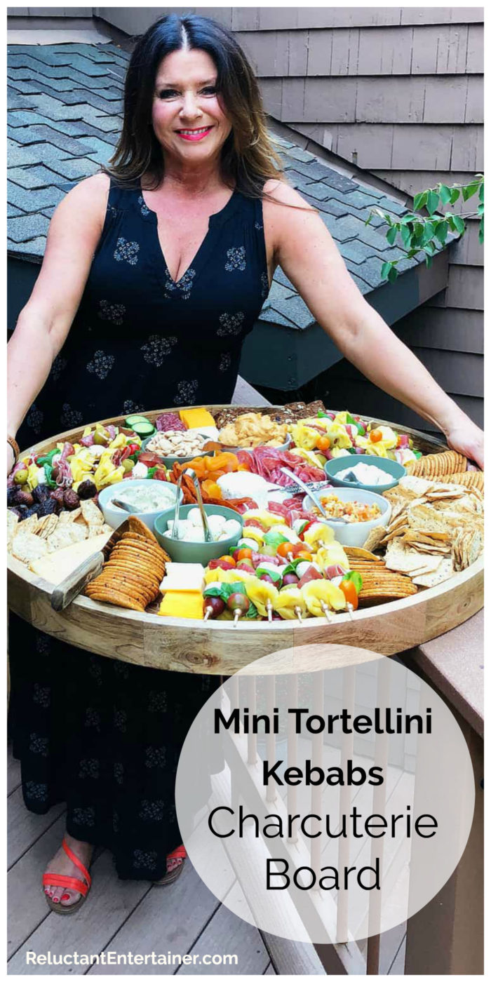 woman outside holding a charcuterie board with mini tortellini kebabs