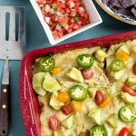 a red 9x13 pan filled with zucchini and cheese enchiladas