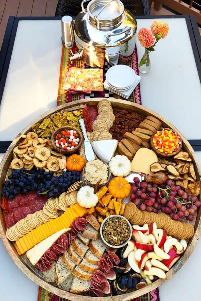 outside setup of Fall Epic Charcuterie Board with beverage and napkins