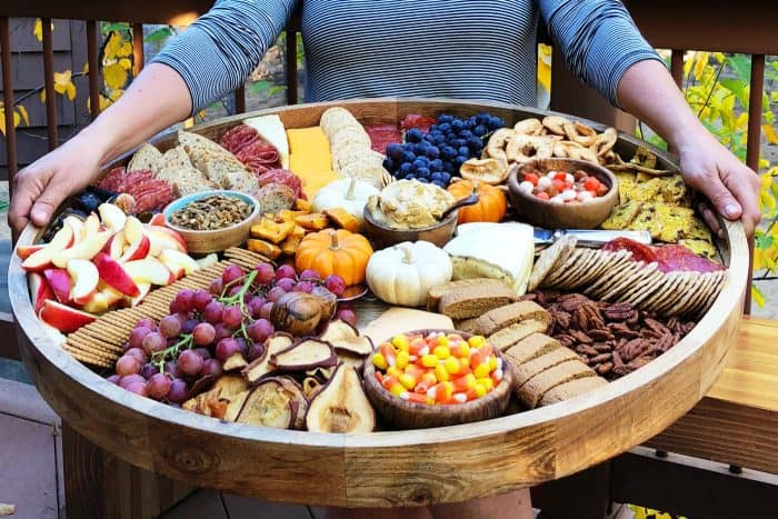 person holding a Fall colored Charcuterie Board