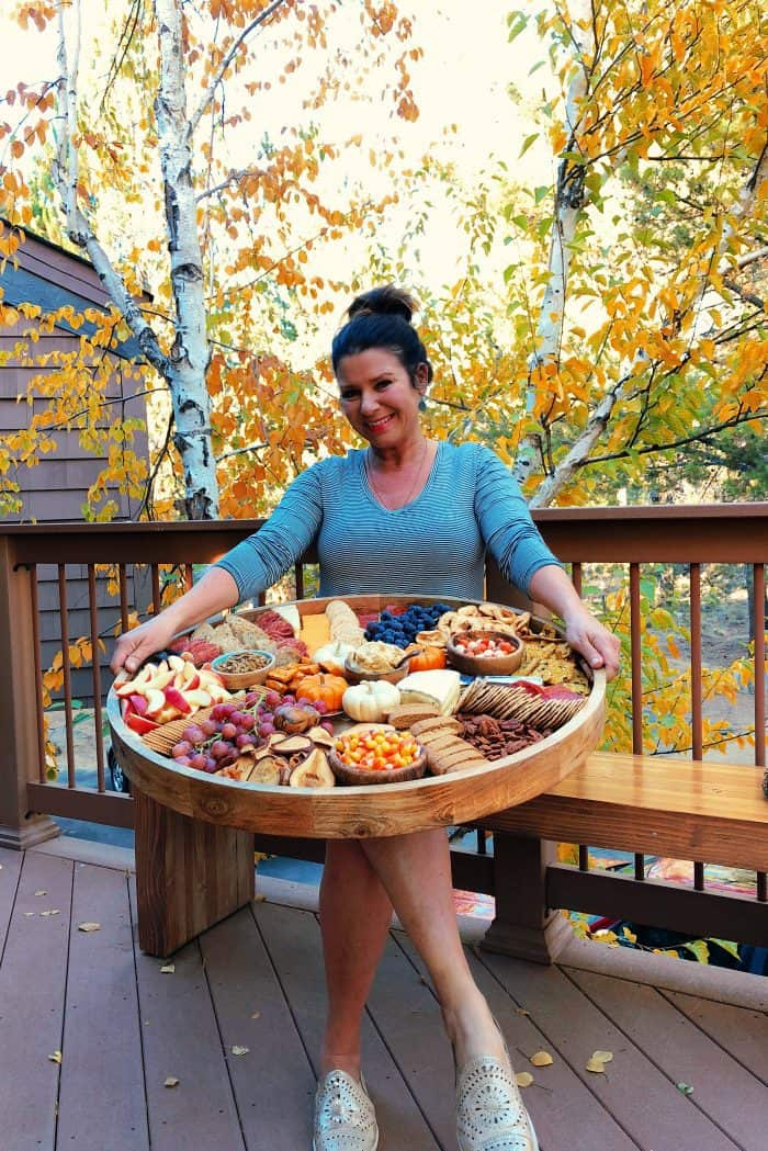 woman holding an Epic Charcuterie Board with fall colors in background