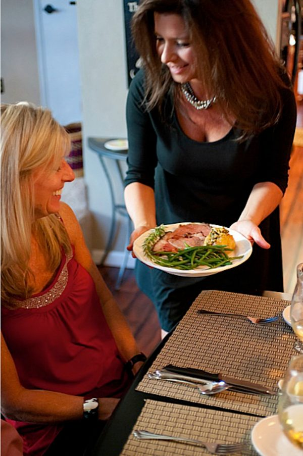 woman serving a plate of prime rib
