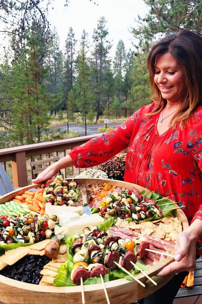 woman holding a big round wood board with appetizers