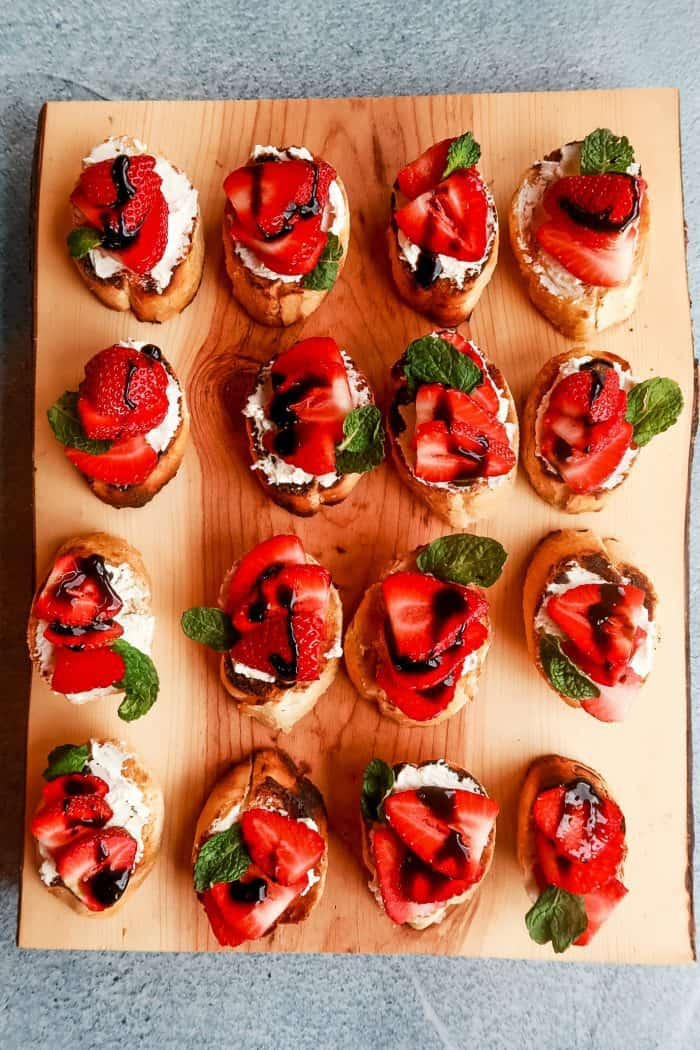 a wood board with 12 beautiful Strawberry Goat Cheese Bruschetta toasts