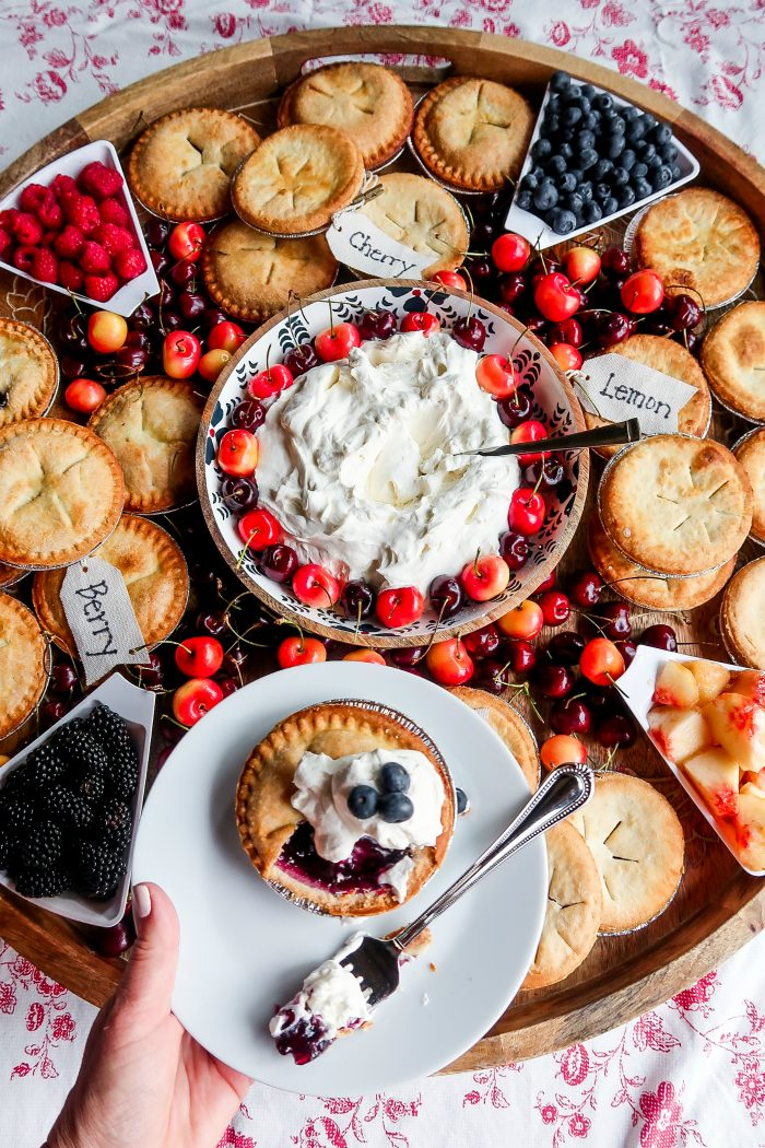 a blueberry mini pie on a plate with whipped cream