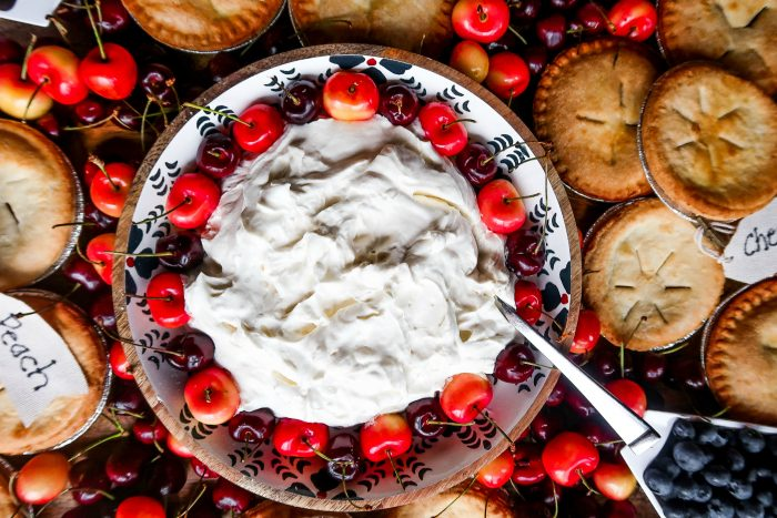bowl of whipped cream and cherries