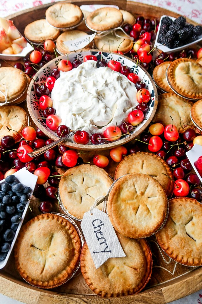 bowl of whipped cream and cherries on a board with mini pies