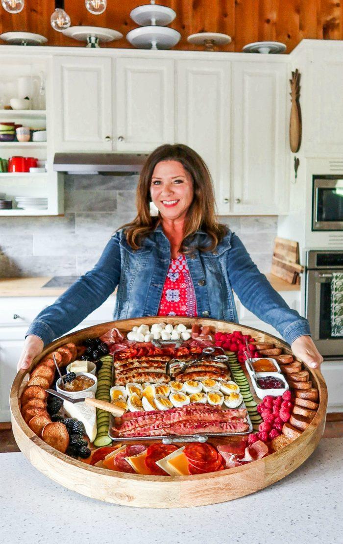woman holding epic wood charcuterie breakfast board