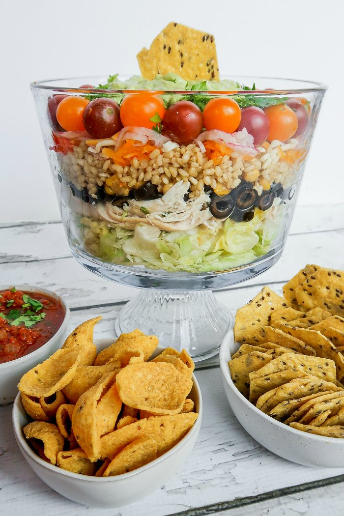 A chicken and rice salad with layers of tomatoes, olives, lettuce, in a glass bowl