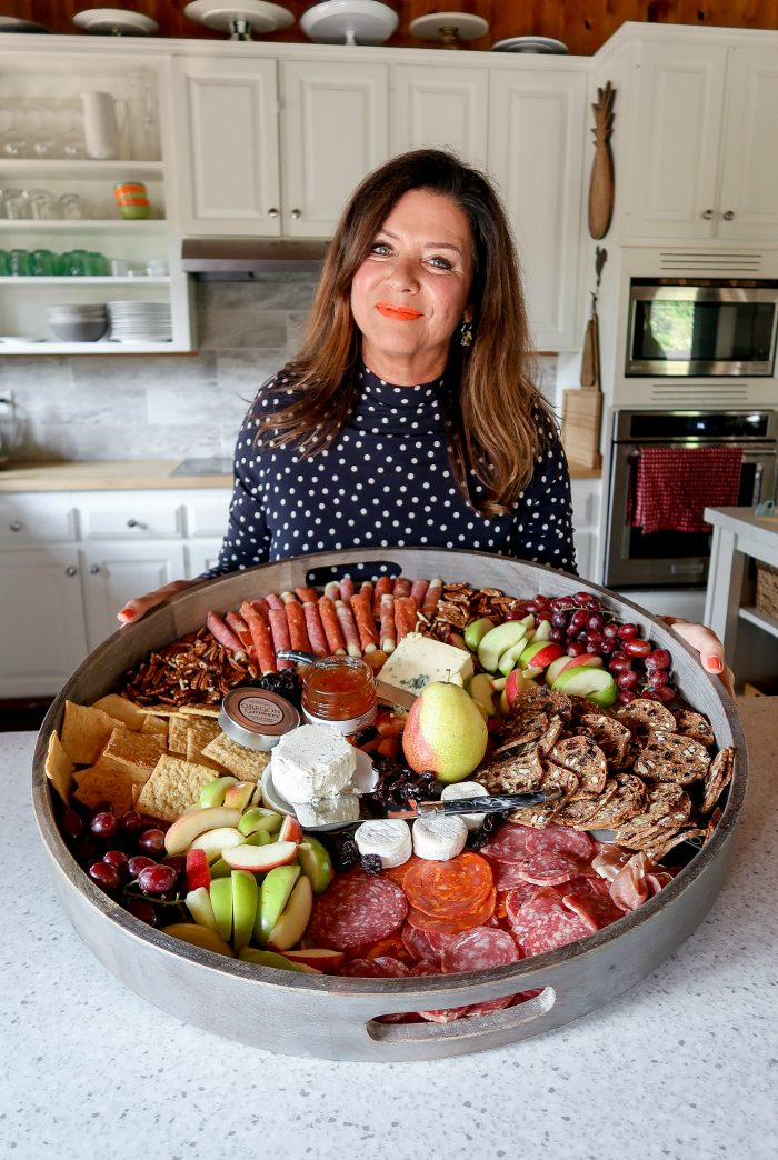 woman in blule polka dot dressing holding a very large Fall Charcuterie Board