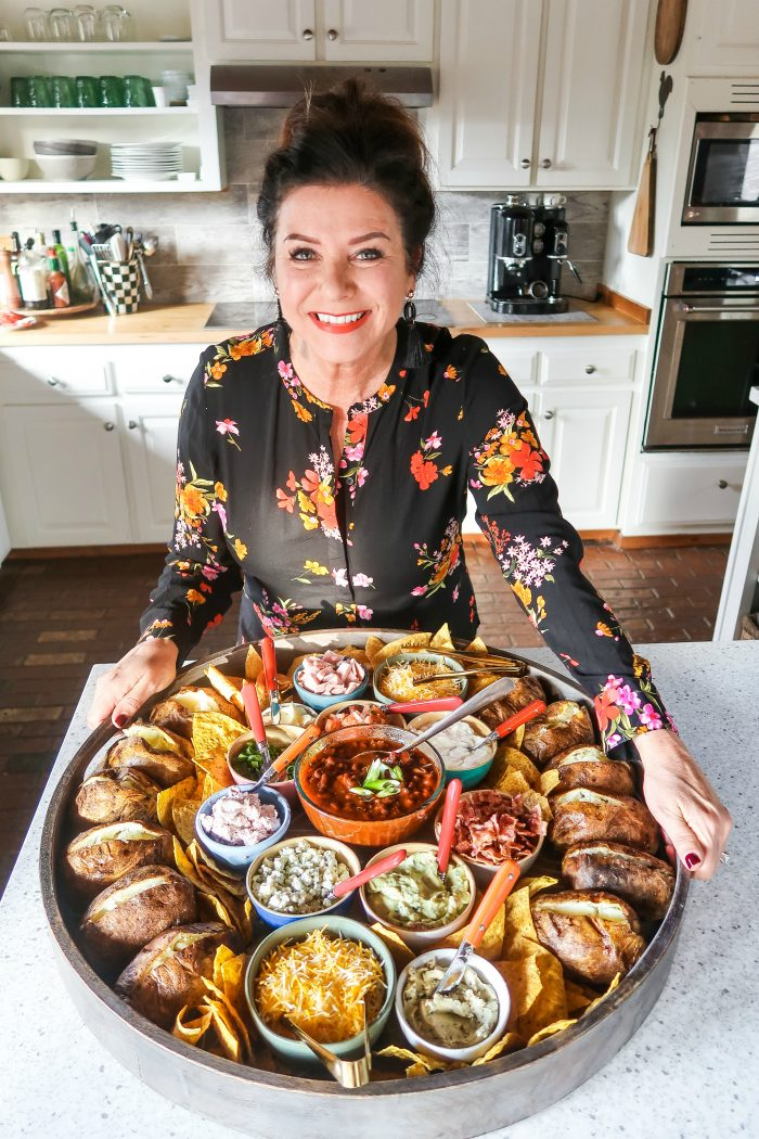 woman holding an epic round wood board with baked potatoes and small bowls of toppings