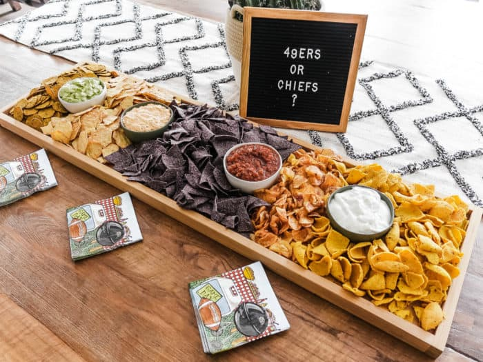 a party rectangular 42 x 12 inch board filled with chips and dips