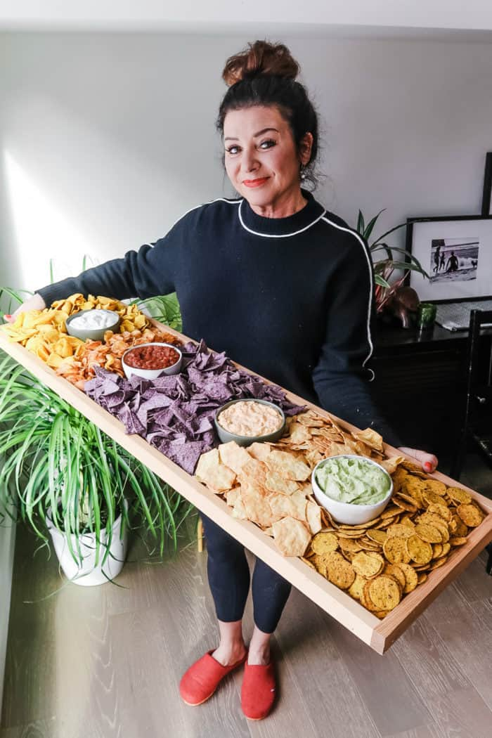 woman holding a 42 x 12 inch board filled with chips and dips