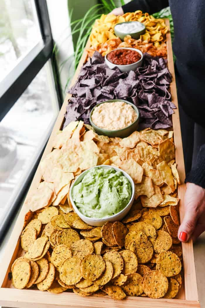 a rectangular 42 x 12 inch board filled with chips and dips