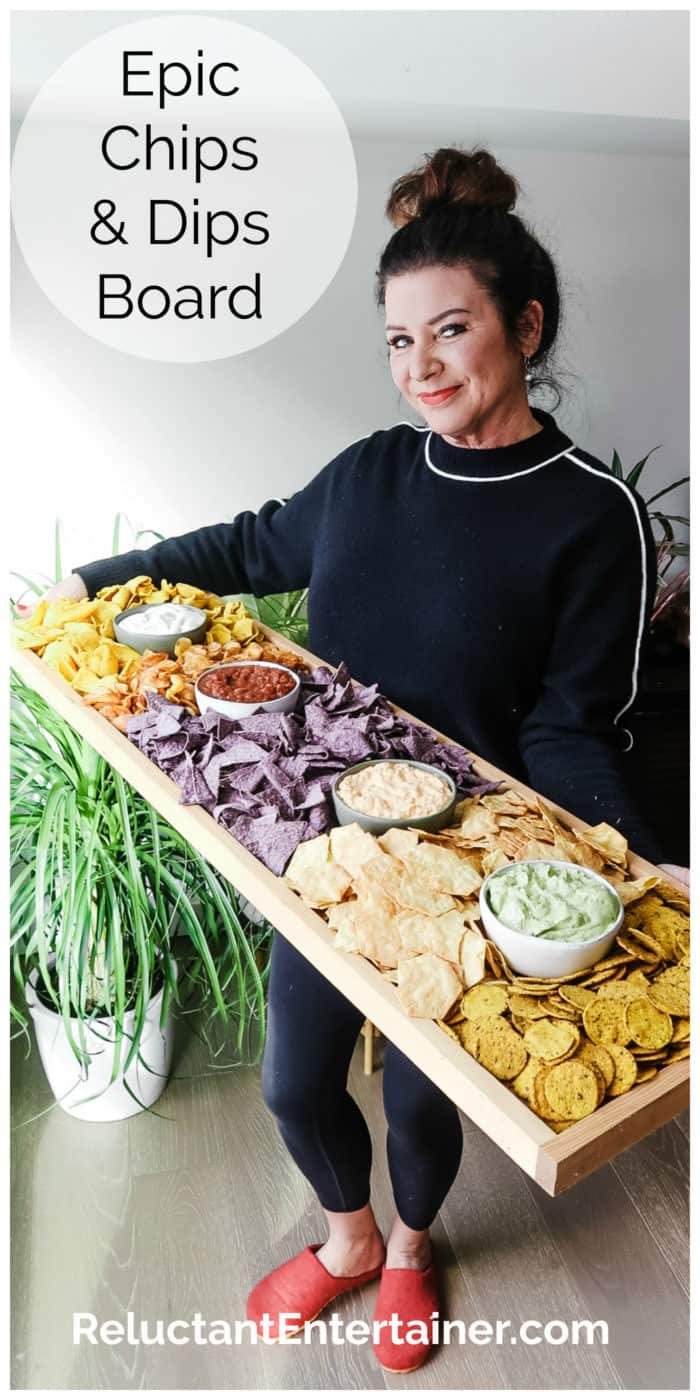 woman holding a rectangular 42 x 12 in board with chips and dips