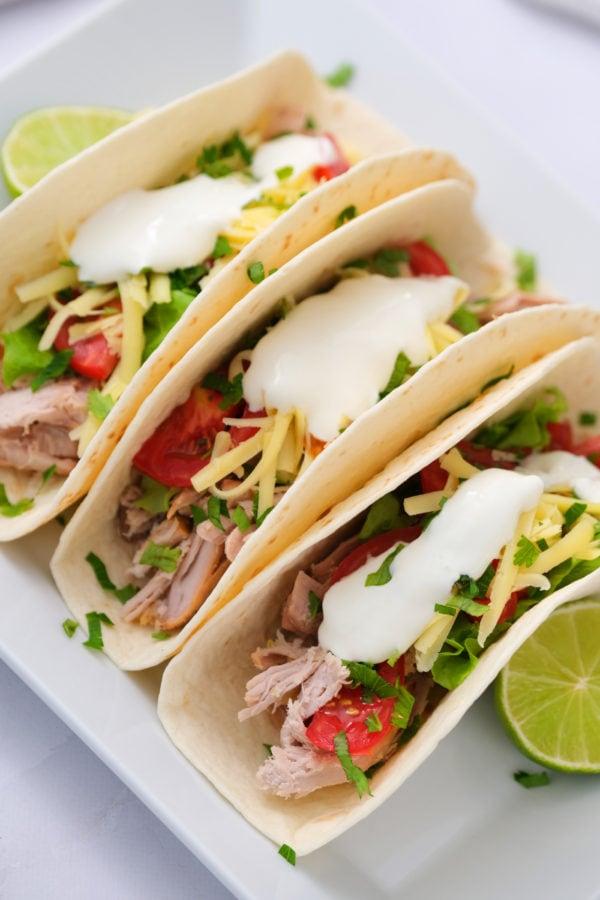 2-Ingredient Crock Pot Pork Verde served in tacos