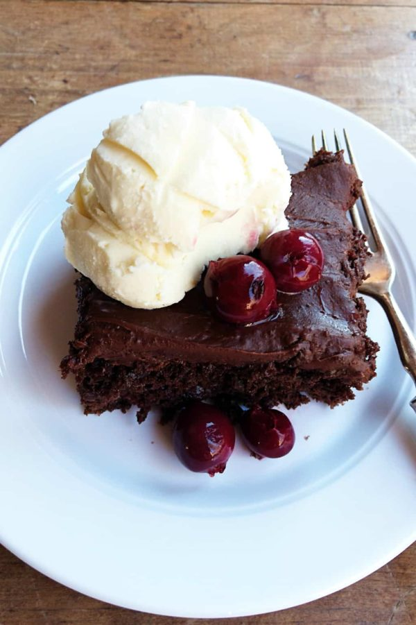 piece of chocolate cake with cherries on top with ice cream