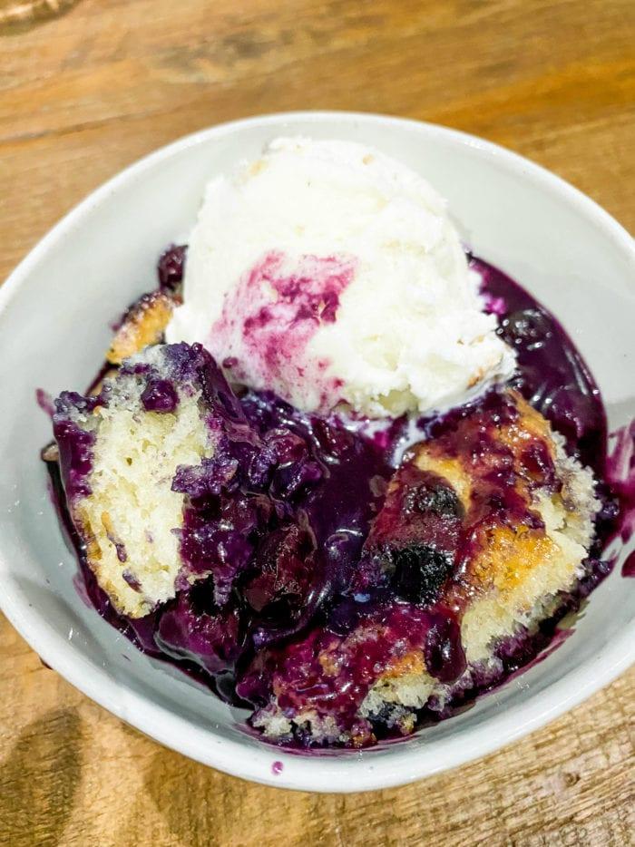 bowl of blueberry cobbler with vanilla ice cream
