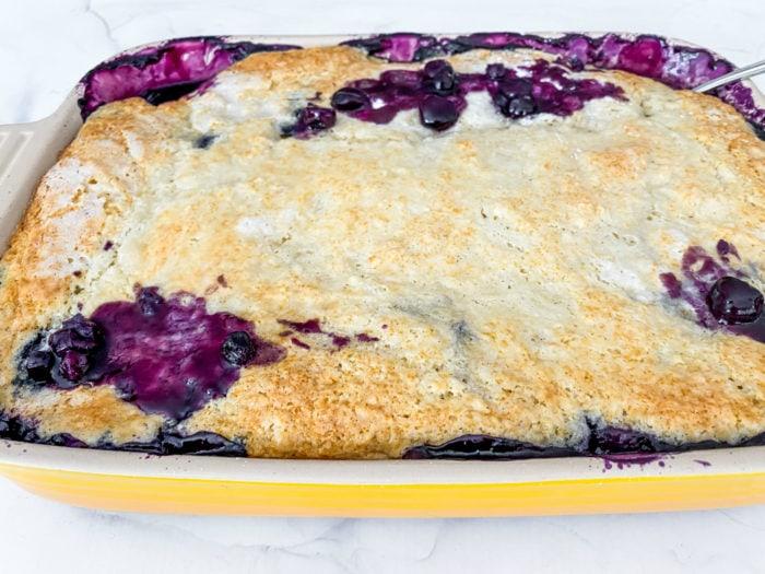9x13 yellow pan of juicy blueberry cobbler