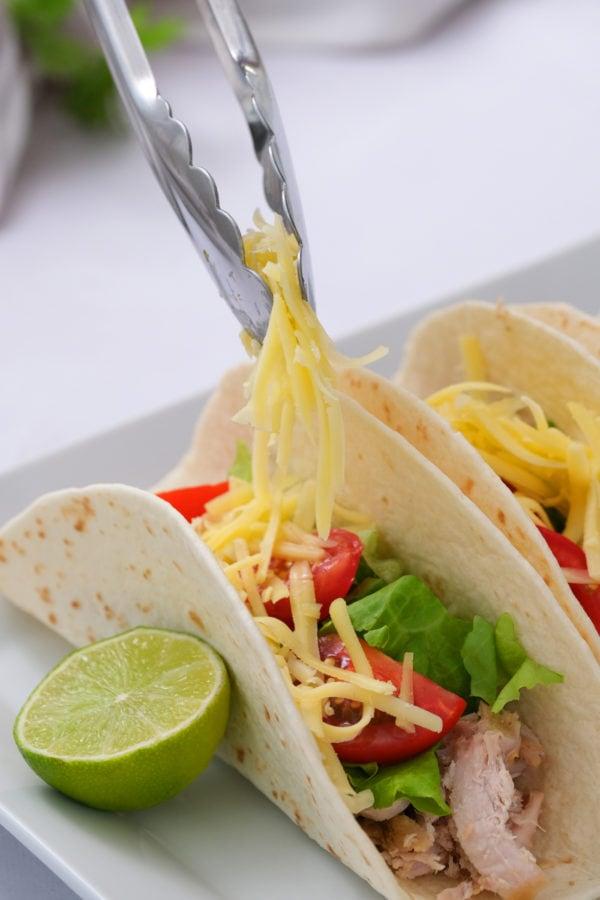 adding cheese to 2-Ingredient Crock Pot Pork Verde tacos