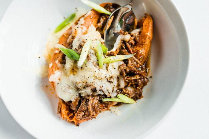 a sweet potato with chuck roast, cheese, and chives