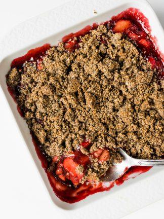 large spoonful of rhubarb and strawberry crisp with poppyseed topping