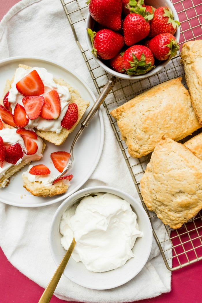 looking down on a plate of strawberry shortcake, a bowl of whipped cream, and shortcakes